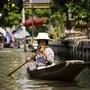 [1] Một cụ bà đang chèo thuyền trên khu chợ nổi.